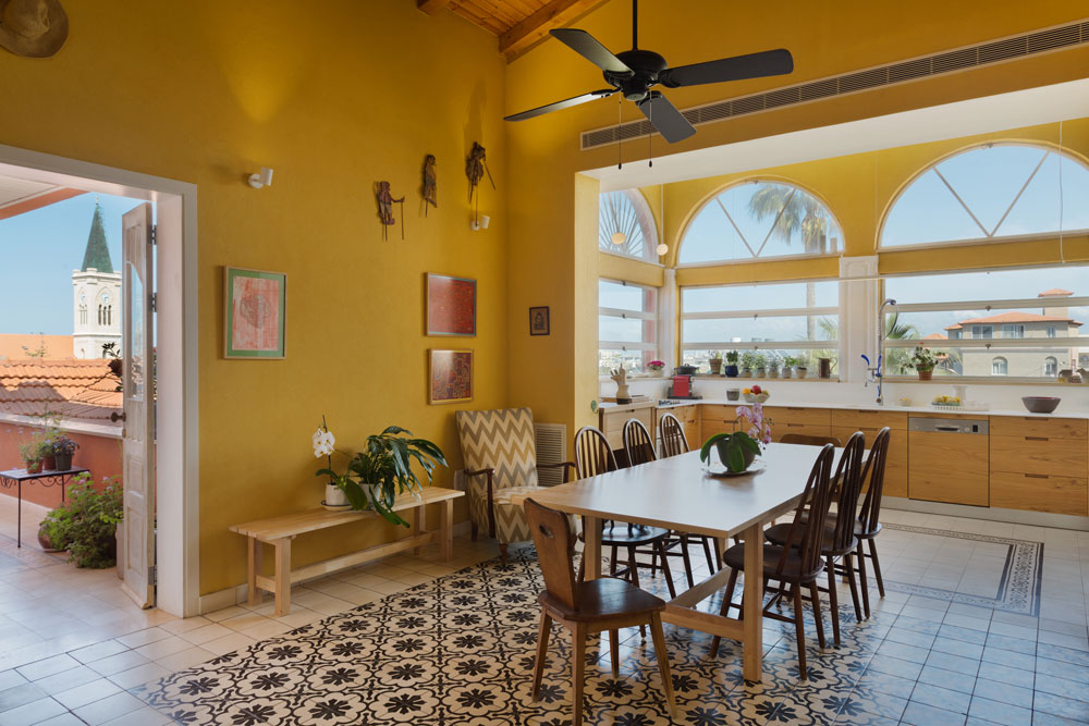 """סקלת הצבעים במטבח היא חמימה, ושטיחי האריחים על הרצפה נשמרו, ברוח יפואית. השולחן הגדול נקנה ב""""איקאה"""", הכסאות, הכורסה והארון הם משוק הפשפשים. על הקירות תלויות שתי עבודות רקמה שיצרה סבתה של בלינדר וציור גדול של נעמי מנדל (שאותו אפשר לראות בתמונה העליונה) (צילום: אסף פינצ'וק)"""