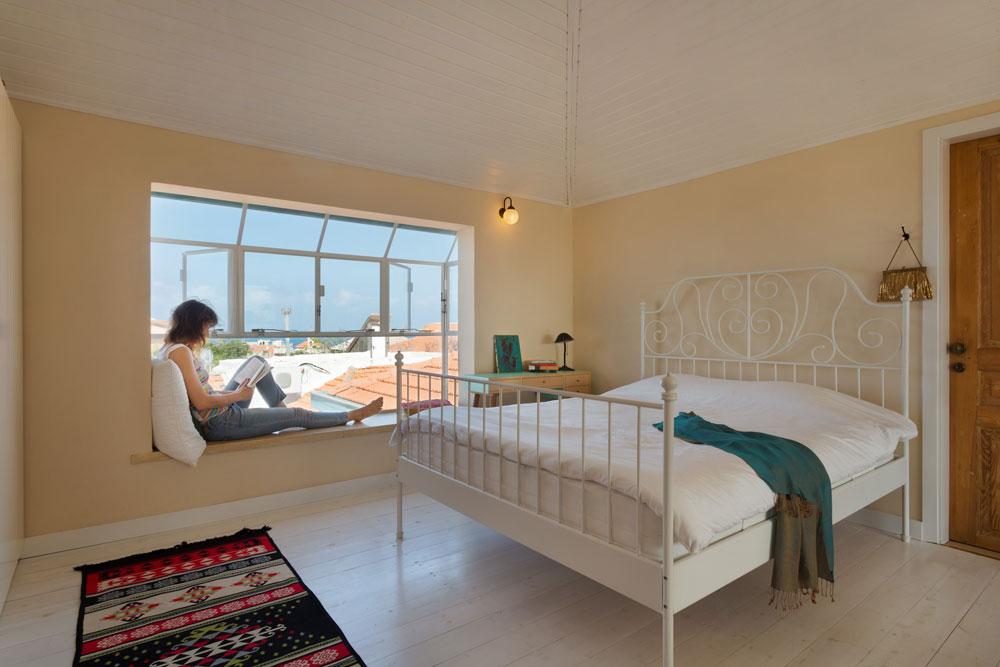 """חדר השינה של בלינדר במפלס העליון של הבית. המיטה מ""""איקאה"""", השולחן משוק הפשפשים והתקרות חופו מחדש בקורות עץ שנצבעו לבן. החלון ''נדחף'' החוצה כדי ליצור ספסל שמשקיף אל הנוף, ומולו, בצדו השני של החדר, רחבת היציאה למרפסת שמופיעה בתמונה הקודמת משמאל (צילום: אסף פינצ'וק)"""