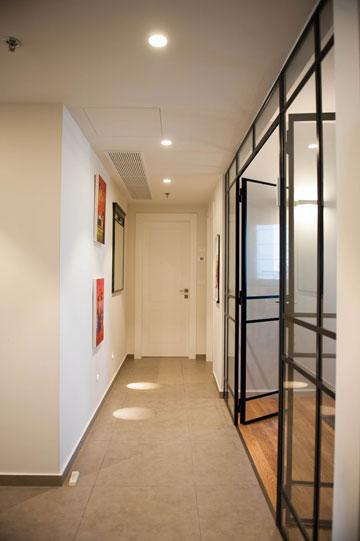 אור טבעי מגיע למסדרון מכיוון חדר העבודה, שנסגר בקירות זכוכית קבועים בתוך פרופיל בלגי שחור (צילום: גלעד ארדט)