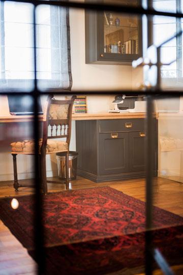 חדר העבודה: ארון עם דלתות זכוכית מחולקות לריבועים (התמונה מצולמת דרכן), שולחן מפלטת עץ גושני ומגירות שחורות (צילום: גלעד ארדט)
