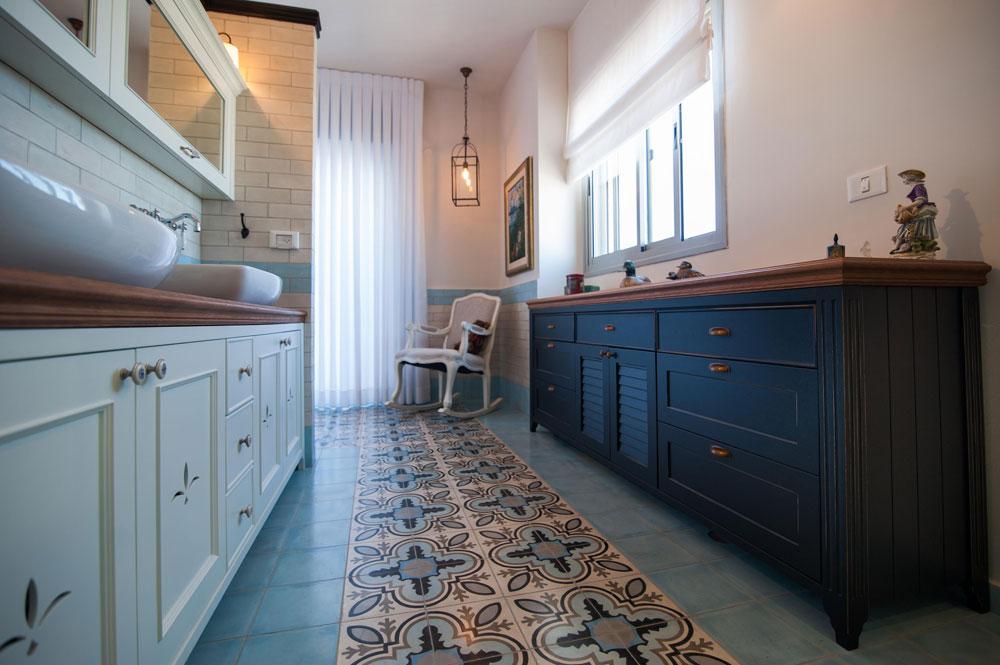 """בחדר הרחצה של ההורים חופו הקירות באריחים בצורת לבנים בצבע לבן. הרצפה חופתה באריחי בטון בגוון טורקיז, ובמרכז עוצב """"שטיח"""" מאריחים מעוטרים בגוונים משלימים. ארון המקלחת (משמאל) תוכנן בסגנון כפרי ונצבע בלבן. שני כיורים הונחו על משטח עץ, ומעליהם נתלו ארונות. ממול הוצבה שידה שנצבעה בשחור. לצד השידה, כיסא נדנדה ומעליו שנדליר (צילום: גלעד ארדט)"""
