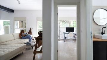 מבט מכיוון חדר הארונות אל חדר הרחצה (מימין), חדר העבודה (ממול) והסלון (צילום: טל ניסים)