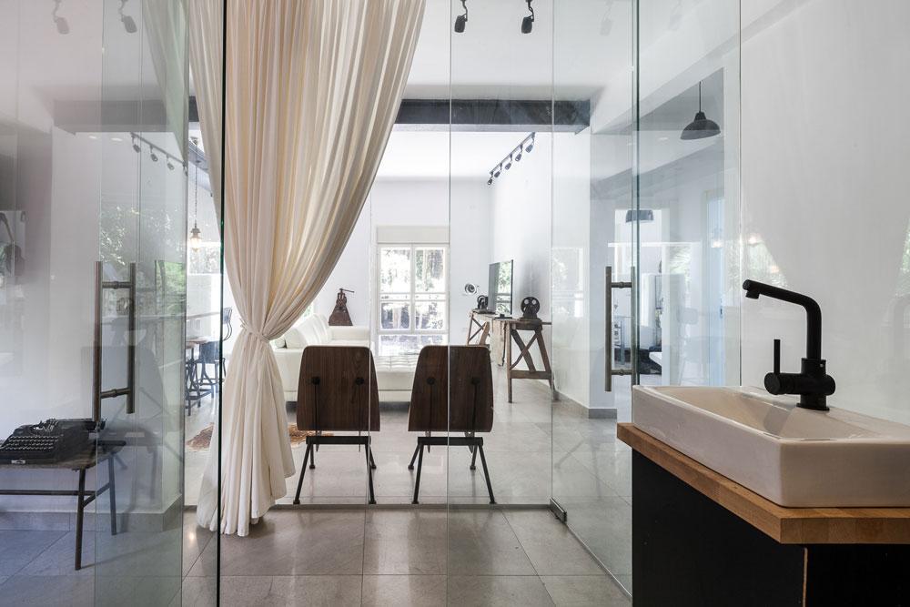 מבט אל הסלון מכיוון פינת הרחצה הצמודה לחדר השינה, שמוקפת קירות זכוכית. כסאות העץ שבמרכז התמונה נשענים על מחיצת הזכוכית שמפרידה בין הסלון לחדר השינה (צילום: טל ניסים)