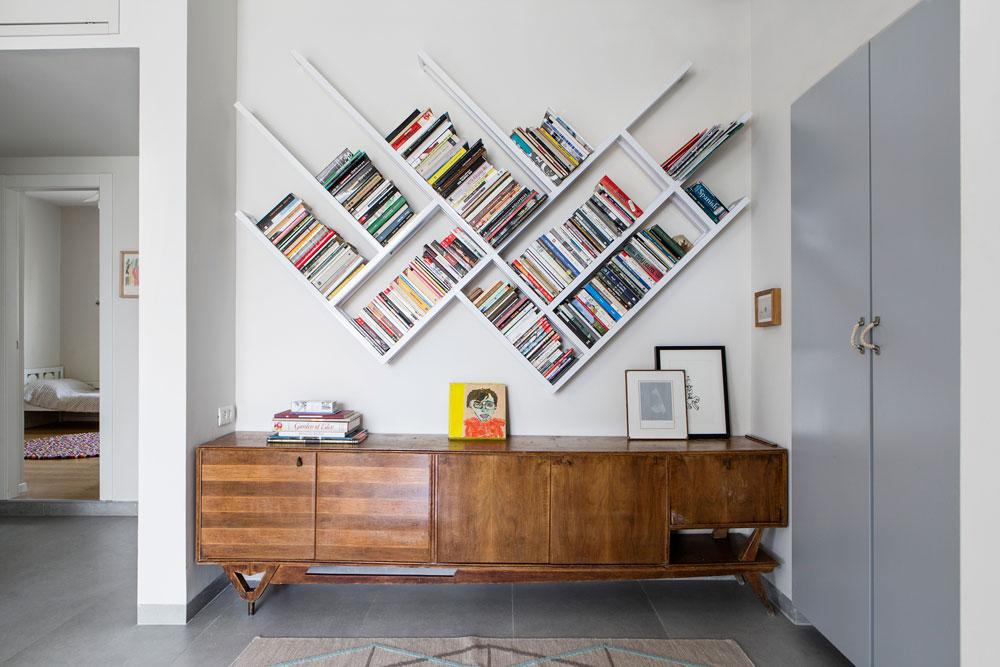שידה משנות ה-50, שנמצאה בדירה הישנה, מצאה את מקומה מחדש אחרי השיפוץ, מתחת לספריית ברזל בקווים אלכסוניים (צילום: איתי בנית)