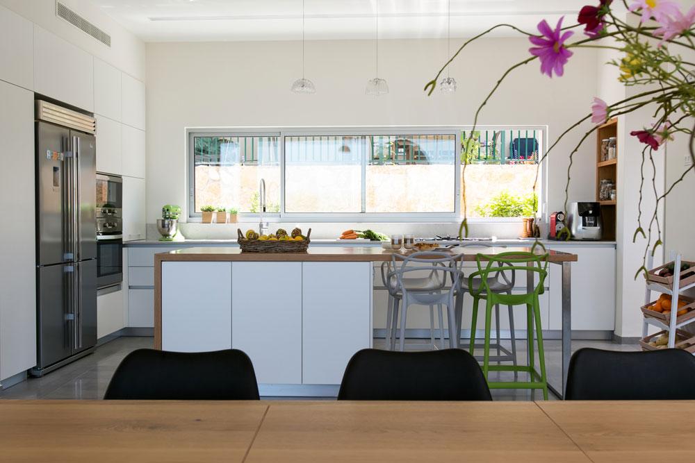 המטבח פונה לחצר האחורית וכולל ארונות פורמייקה גבוהים ונמוכים. במרכז הורכב אי, שחזיתו לכיוון הארונות (שאותה לא רואים בתמונה) מכילה יחידת מגירות ומקרר יין (צילום: שירן כרמל)