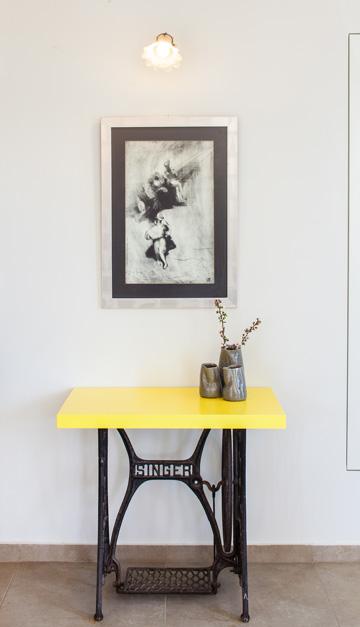 שידה למפתחות במבואה, מבסיס ישן של מכונת תפירה ופלטה שנצבעה בצהוב (צילום: טל ניסים)