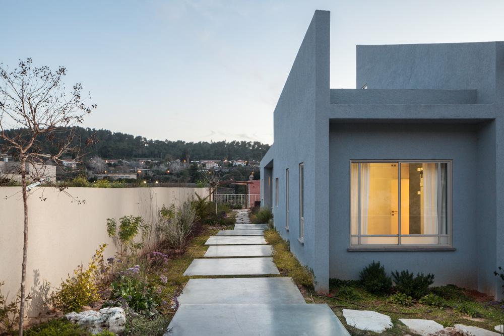 שביל של ריבועי בטון מוביל לדלת הכניסה. לאחר שהבית נבנה פנו בני הזוג - הורים לשלוש בנות - למעצבת פנים בבקשה ליצירת בית צבעוני, נעים, חם ולא סטנדרטי (צילום: טל ניסים)