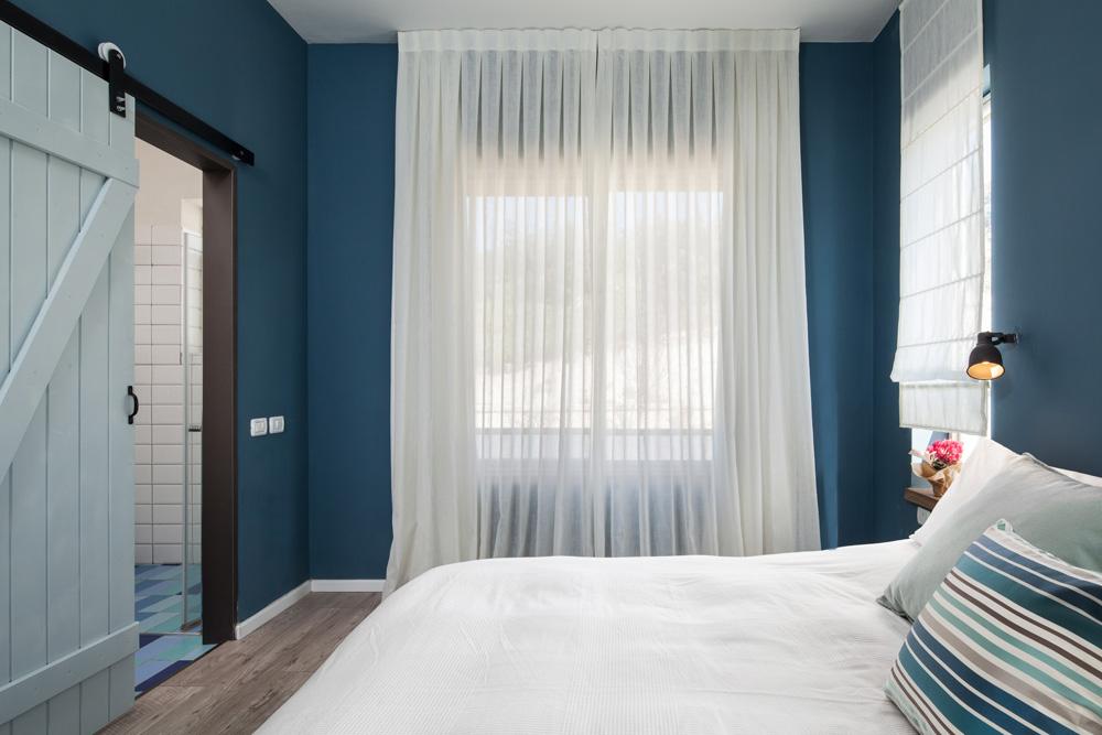 חדר ההורים נצבע בכחול, ומופרד מחדר הרחצה הצמוד בדלת אסם שבעל הבית שיפץ וצבע. היא נוסעת על מסילה חיצונית ובכך חוסכת מקום (צילום: טל ניסים)