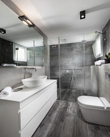 האפור שמאפיין את הדירה כולה נמצא גם בחדרי הרחצה (צילום: אלעד גונן)