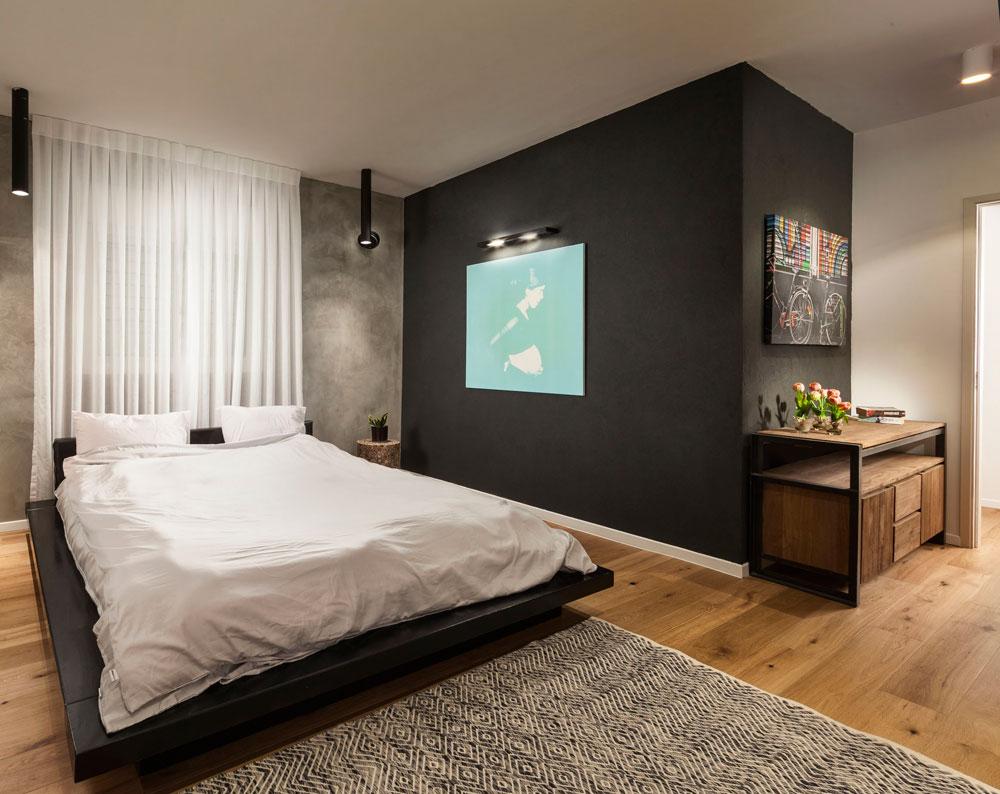 הקיר שבגב מיטת ההורים נצבע באפור, ושחור עוטף קיר אחר ומגדיר מעין מבואת כניסה לחדר (צילום: אלעד גונן)