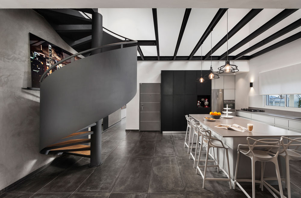 מבט מהסלון לכיוון המטבח ודלת הכניסה. קורות הפלדה הכתיבו את הסגנון, גרם המדרגות לקומת הגלריה נבנה כספירלה, ומאחוריו הכניסה למסדרון שמוביל לחדרי השינה (צילום: אלעד גונן)