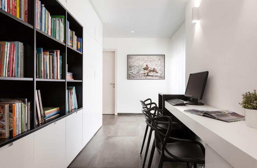 במסדרון שמחבר בין המטבח לחדרים הפרטיים תוכננו פינת עבודה ארוכה וארונות אחסון לבנים עם קובייה שחורה של מדפי ספרים. בקצה יציאה נוספת למרפסת (צילום: אלעד גונן)