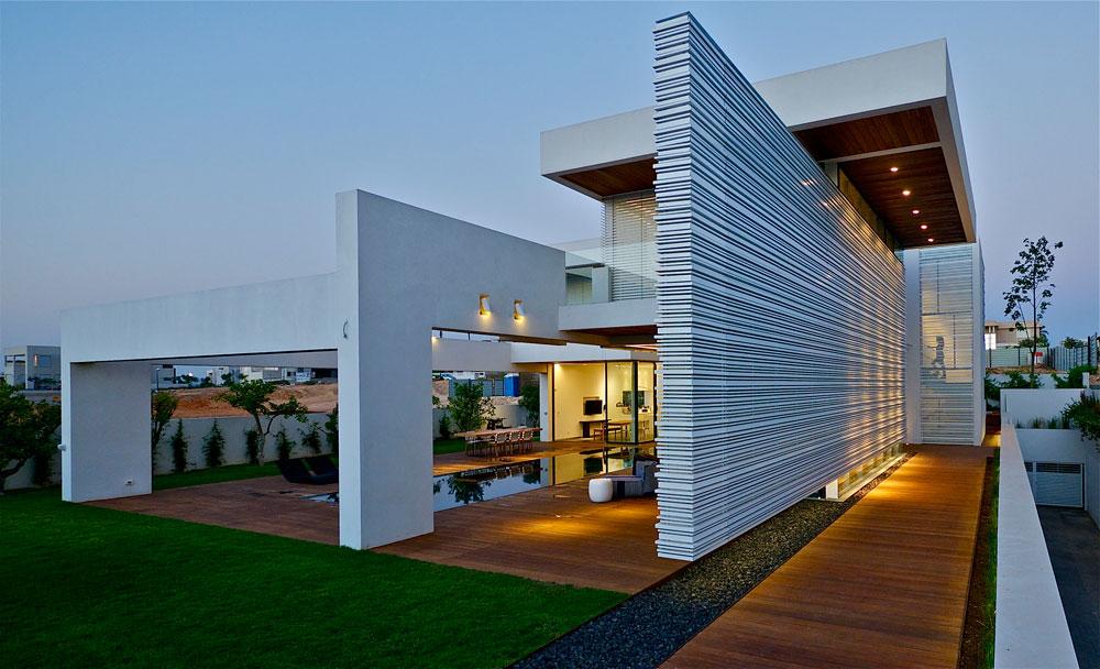המקום: קיסריה. מטראז': 500 מ''ר בנויים על מגרש של דונם. תכנון: אדריכל גל מרום ואדריכלית מאיה רוזנברג. קיר עצום ומרחף מפריד בין הכניסה מהרחוב לחללים הפרטיים בבית, ומאפשר קומת כניסה מרווחת ופתוחה מאוד. הקיר חופה סרגלי אלומיניום לבנים (צילום: איתי סיקולסקי)