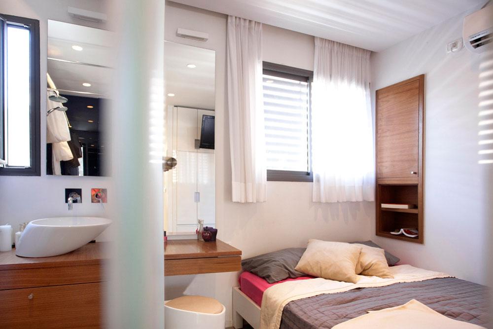 המיטה בחדר ההורים הוצמדה לקיר, כדי לאפשר להם חדר רחצה צמוד. מחיצת זכוכית שחלקה אטום וחלקה שקוף מפרידה בין חלקי החלל, אך לא קוטעת את הזרימה (צילום: גידי בועז)