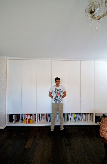 אלון ליבנה בביתו. ''יש לי ארון קיר גדול לאורך קיר שלם, עם שמונה דלתות ענקיות מהרצפה ועד לתקרה'' (צילום: איתי סיקולסקי )