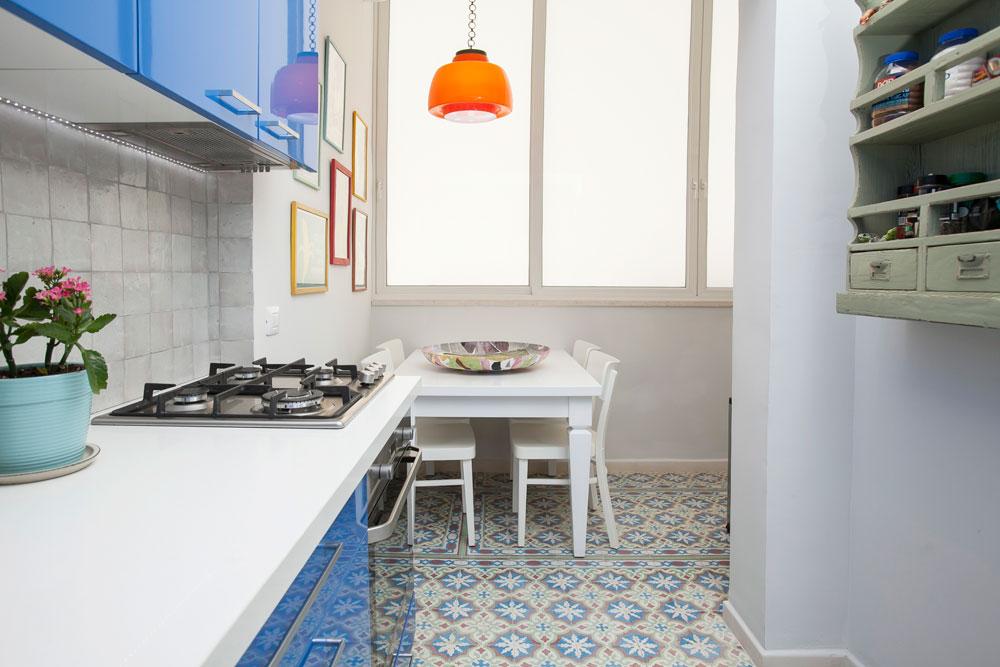 המטבח רוצף באריחי בטון מאוירים, לארונות נבחר כחול אפוקסי מבריק ומעל שולחן האוכל נתלתה מנורת וינטג' כתומה (צילום: שירן כרמל)