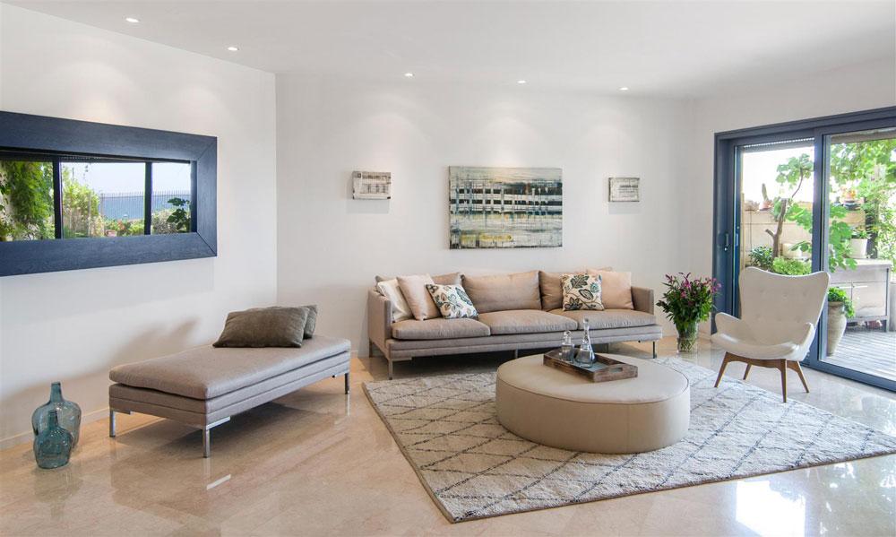 כדי שהדירה לא תיראה לבנה ומנוכרת נבחרו לסלון רהיטים בגוונים חמים ורכים  (צילום: אביב קורט)