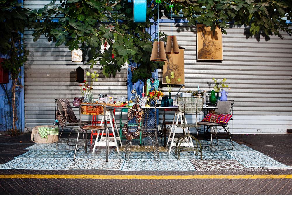 השולחן עומד על פסיפס של שטיחי פי-וי-סי שמודפסים בטכניקה דיגיטלית ומחקים את האריחים האותנטיים המצוירים של פעם: דוגמה קלאסית למיקס-אנד-מאץ' שאפשר להביא הביתה מהשוק (צילום: ענבל מרמרי)