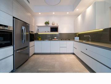 המטבח תוכנן בצורת ח' ועשוי עץ אלון מולבן. הצלע הרביעית פונה לחצר הפנימית (צילום: אילן נחום)