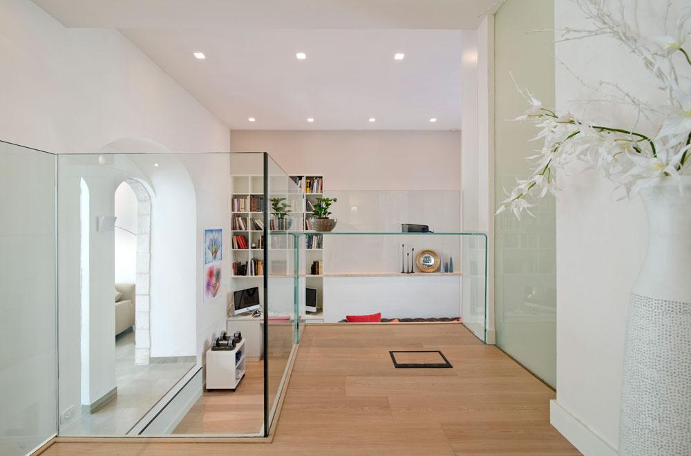 מבט מהגלריה אל חדר המשפחה והעבודה. בבית נעשה שימוש באלמנטים מזכוכית, כמו מעקה ושולחן שקופים, שלא חוסמים את שדה הראייה (צילום: אילן נחום)