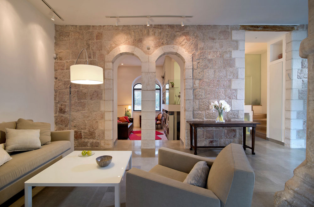 הפתחים המקושתים המקוריים בקיר האבן נפתחו בשיפוץ, לאחר שנאטמו עם השנים. כך נוצר חיבור ויזואלי בין שני חלקי הדירה. בתמונה: מבט מכיוון הסלון לחדר המשפחה והעבודה, שנמצא במורד שלוש מדרגות. מימין עלייה לגלריה שבה חדר השינה של בעלי הבית, עם חדרי רחצה וארונות צמודים. רוזנשיין בחר לשלב ישן בחדש, ולכן נבחרו רהיטים וגופי תאורה מודרניים (צילום: אילן נחום)