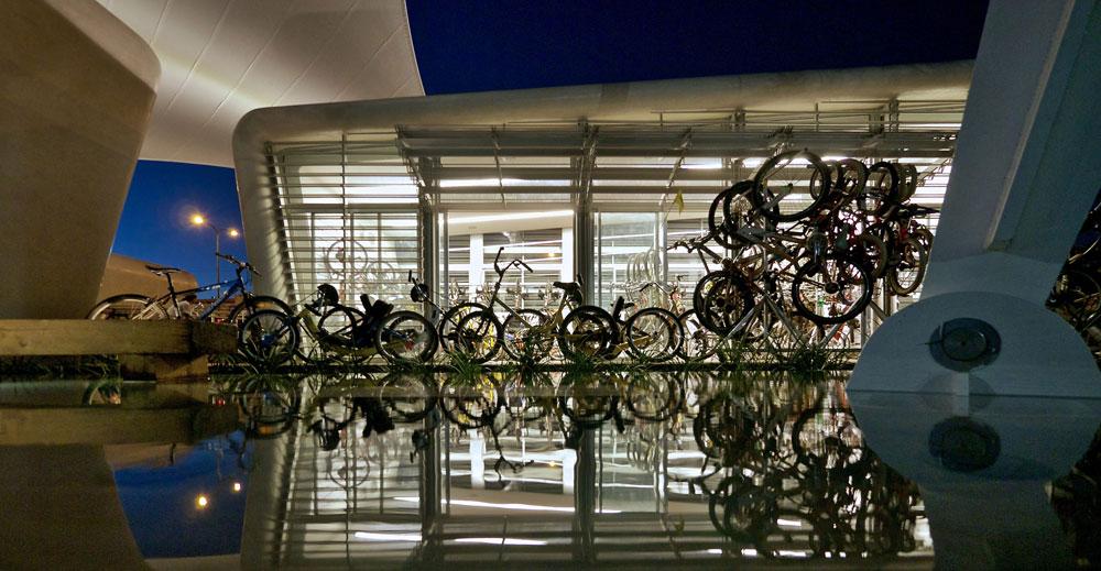 בשעות הערב מאירים המבנים מבפנים החוצה. מחסן האופניים מאחסן 110 אופניים המותאמים לבעלי מוגבלויות שונות, ושלושת המבנים השקופים מאפשרים קשר-עין ותנועה נוחה ביניהם (צילום: איתי סיקולסקי )