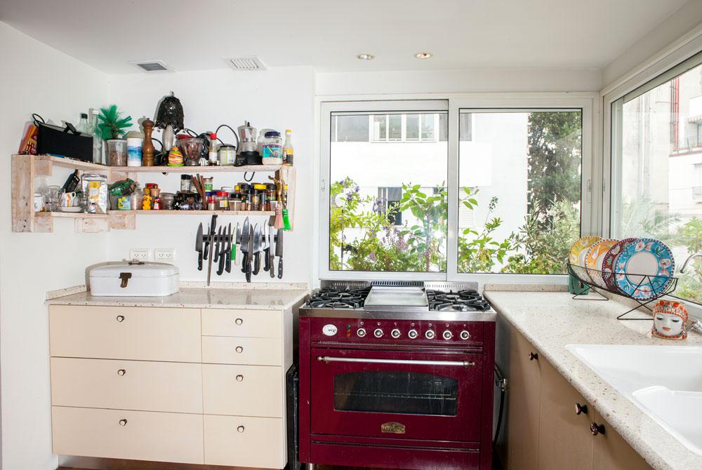 תנור בישול אדום מאיטליה ומעמד ישראלי ישן לכלים. מבט נוסף למטבח (צילום: אבישי פינקלשטיין)