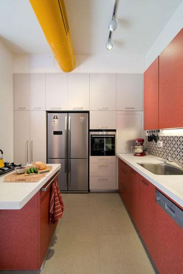 המטבח נצבע בצבעי תבלינים ותעלת המיזוג הושארה חשופה, כדי שלא לפגוע בגובה התקרה (צילום: אילן נחום)