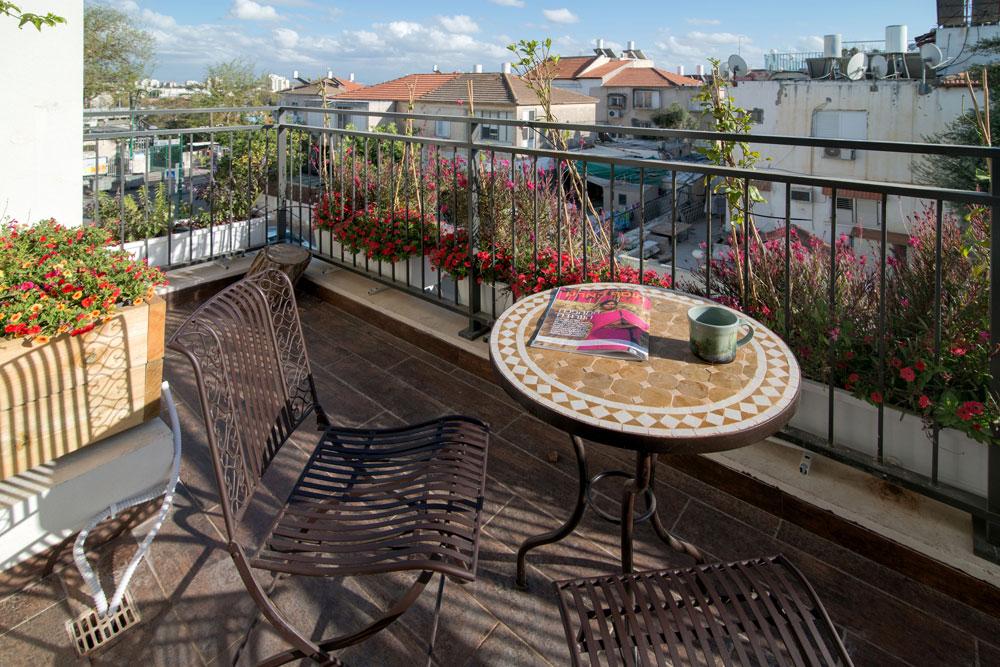 מראה מהמרפסת אל השכונה, שמתאפיינת בבתים ישנים נמוכי קומה, שלא מפריעים לבריזה להגיע מחוף הים (צילום: אילן נחום)