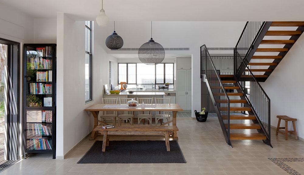 ארונות הגובה שבמטבח מוקמו מול גרם המדרגות המוביל לקומת חדרי השינה ומטשטש את מסת הנגרות שנחשפת לעיני הנכנסים. מעל שולחן האוכל נתלו שני גופי תאורה שחורים של המותג ההולנדי moooi. קומת הכניסה רוצפה באריחי בטון בגון חול. במבואה שולבה בריצוף מסגרת של אריחים מעוטרים בצבעי חום וירוק (צילום: אלעד שריג)