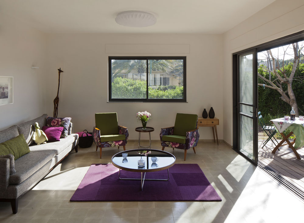 הסלון פונה לחצר הנראית מחלון זכוכית גדול. פינת הישיבה - בצבעים של אפור, סגול וירוק - נהנית מרוח הים שנכנסת דרכו (צילום: אלעד שריג)