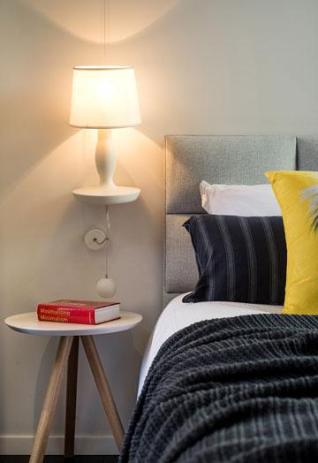 מנורת קיר דקורטיבית מגבס לצד המיטה (צילום: אביב קורט)