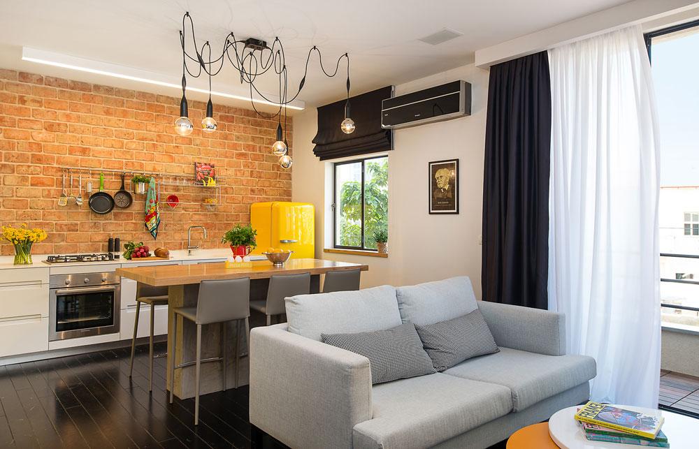 הספה הועמדה במרכז החדר, כשגבה אל ''אי'' העבודה והאכילה. מעליו נתלתה מנורה בעיצובו של האדריכל ז'אן נובל (צילום: אביב קורט)