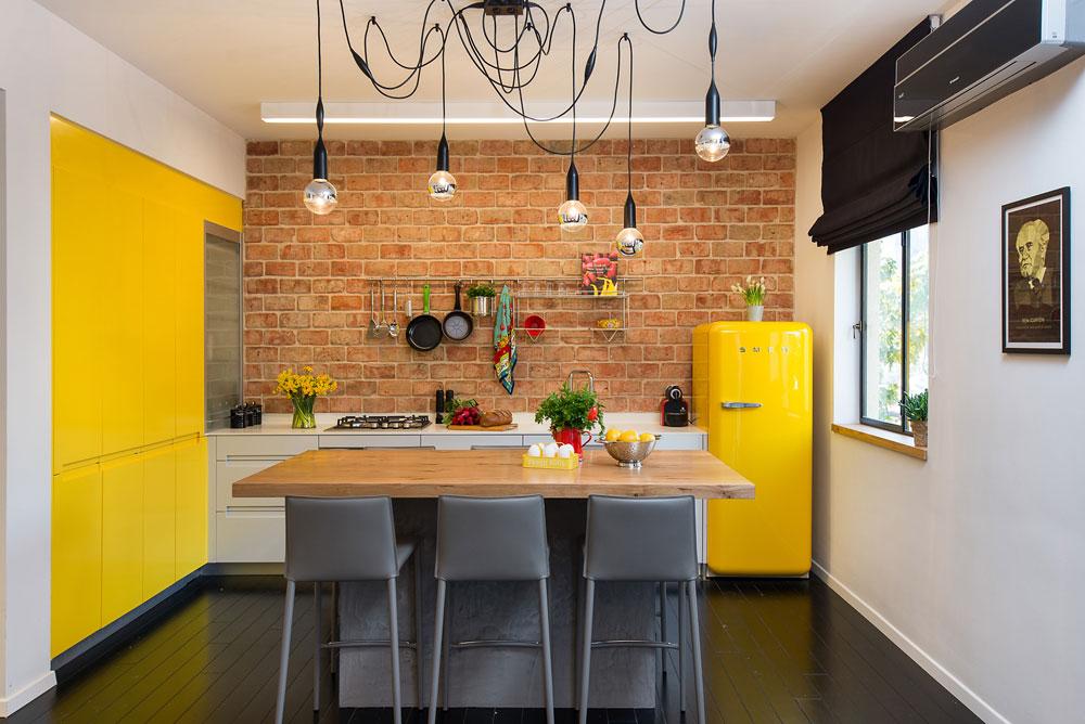 ארונות המטבח תוכננו בצורת האות ר': על קיר הלבנים האדמדמות פס של ארונות לבנים נמוכים, ולצידו ארונות גבוהים בצהוב, כצבע המקרר (צילום: אביב קורט)