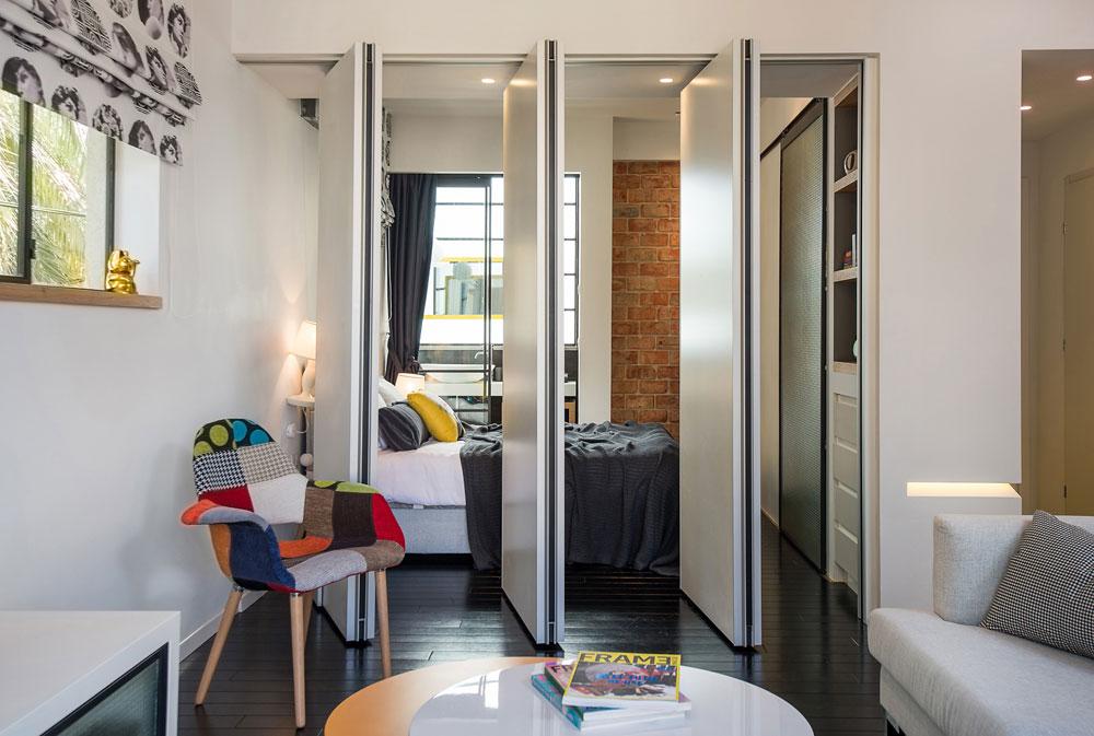 מבט מהסלון לחדר השינה, שביניהם מפרידות שלוש מחיצות לבנות (ומבודדות אקוסטית). אפשר לסגור אותן ולהפריד בין החדרים, או לפתוח ולהסיט אותן הצידה, כך שנוצר מרחב פתוח (צילום: אביב קורט)