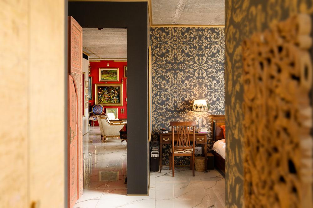 מבט מתוך חדר השינה של בעלת הבית, שבינו לבין הסלון מפרידה דלת מרוקאית עתיקה. הקיר סביבה נצבע באפור-גרפיט, ובגב המיטה טפט שמשלב זהב באותו גוון של אפור (צילום: גדעון לוין)