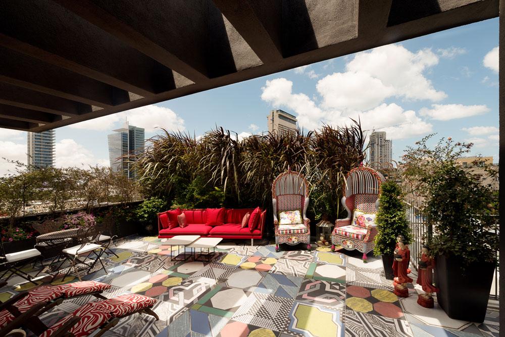 למרפסת הסלון נבחרו שתי כורסאות גרנדיוזיות, שמצליחות לתת מענה הולם לאריחי הבטון המצוירים, מעשה טלאים מתוך קולקציה שלמה (צילום: גדעון לוין)