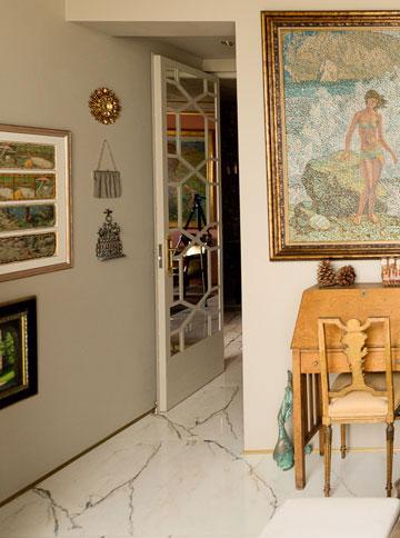 מאות הפריטים שובצו בקפידה: כאן ליד הדלת מראה עגולה וזהובה מפרו, תיק יד משנות ה-40, שהיה של אמה של בעלת הבית, וחנוכייה ממרוקו (צילום: גדעון לוין)