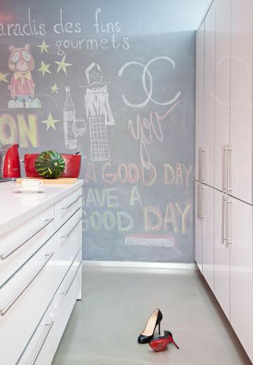 פינה מעבודה של סימונוב ומבט לקיר במטבח הצבוע בצבע לוח (צילום: ינאי דיטש)