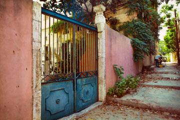 הסמטה ושער הברזל שמובילים לבניין. בצד השני יש חצר נעימה שמוקפת בניינים ותוספות בינוי מתקופות שונות (צילום: ענבל מרמרי)