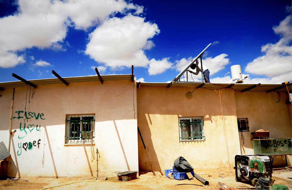 אין חיבור לרשת החשמל בכפר אלזרנוג אבו קווידר, ולכן נעזרים במערכות סולאריות. בעזרת חבל, מזיזים את הקולטים במהלך היום כדי שיופנו אל השמש בזווית המתאימה (צילום: אבי פז)