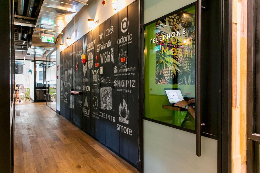 ארון החשמל במסדרון כוסה בלוח גיר, עוד אלמנט מעולם המסעדנות, שעליו שורטטו לוגואים של החברות שנמצאות במקום עכשיו (צילום: שירן כרמל)