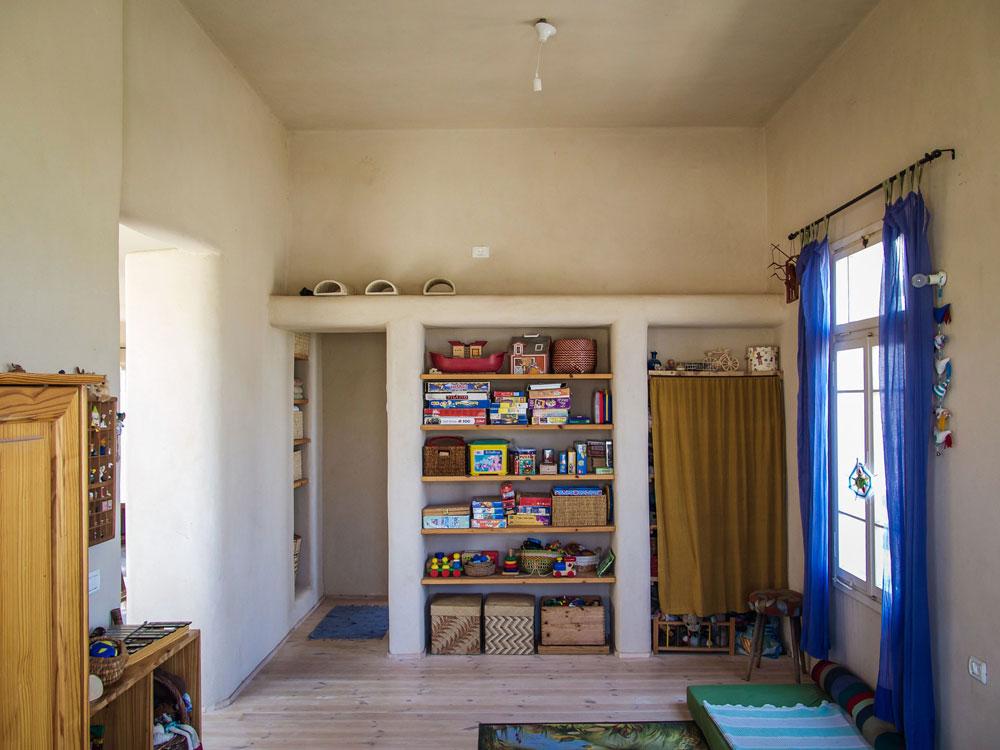 חדר הילדים. ברחבי הבית, רהיטים ופריטים שבני הזוג אספו, ירשו או שיפצו. יש גם פריטים משוק הפשפשים, כמו שטיחים וכוננית (צילום: איתי סיקולסקי)