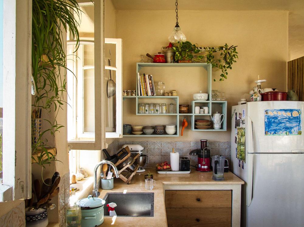 המטבח. על ארונות העץ מונח שיש חלילה. החלונות במטבח, וכמוהם דלת הכניסה, פורקו מבניינים היסטוריים. גם במטבח וגם במקלחת יש אריחים מרוקאיים (צילום: איתי סיקולסקי)