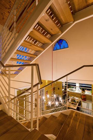 ישורת המדרגות בקומת הביניים והחלון שנחשף בשיפוץ וזוגג בכחול (צילום: אסף פינצ'וק)