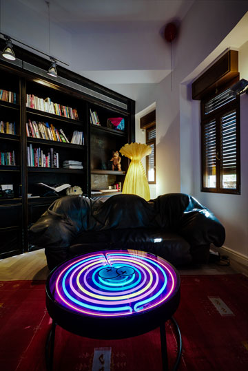 שולחן עגול המואר על ידי נורות ניאון צבעוניות המונחות בתוכו, שעיצב בנה הבכור של אוברזון, רועי (צילום: איתי סיקולסקי)
