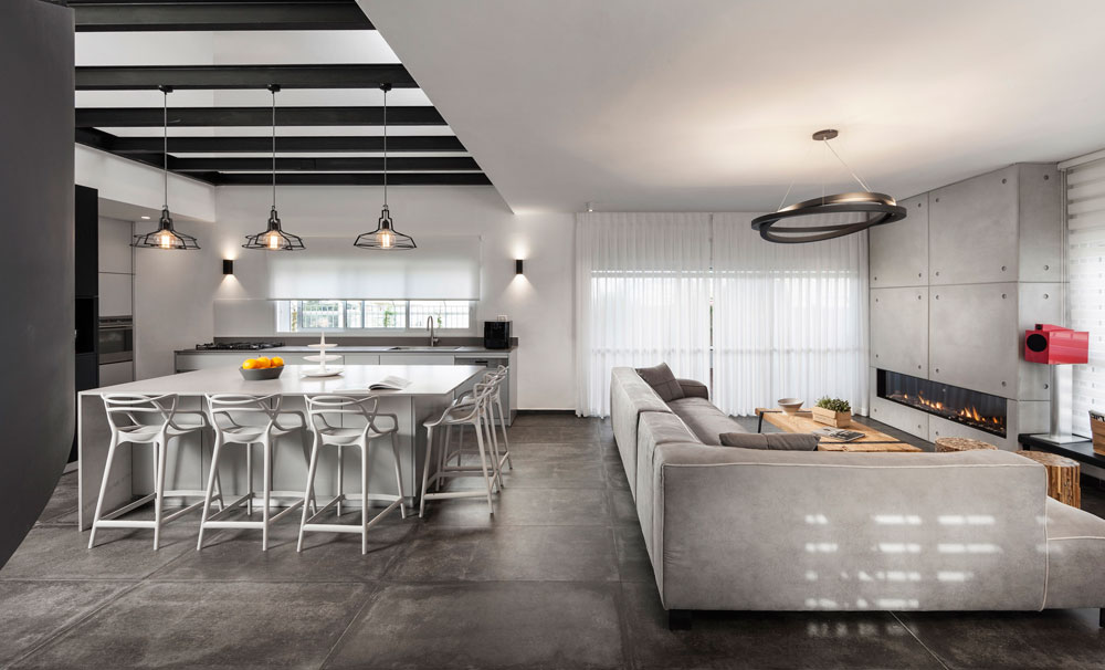 האפור מאפיין את הדירה, לבקשת בני הזוג, בעלי מקצועות חופשיים עם חיבה לעיצוב מודרני. בסלון אין טלוויזיה, אלא קמין שמתפקד כמקום התכנסות משפחתי (צילום: אלעד גונן)