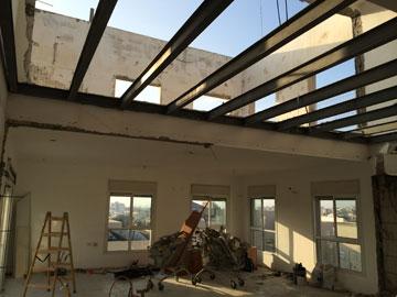 כך נראה הסלון במהלך השיפוץ, כאשר הוסרה תקרת הגבס בין המטבח לקומת הגלריה (באדיבות עדי ארונוב)