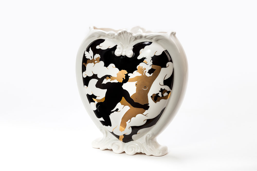 """""""אינטימיכד"""" של אמני הקרמיקה מיי ובועז קאהן והמאייר ניב תשבי עוצב בהשראת הבארוק, הרוקוקו והניאוקלאסיקה. הכד הופשט מהצבעים העזים שאפיינו את הכלים בסגנונו והפך ללבן, מבריק ונקי – מסגרת לאיור כתמים עכשווי ומדויק שהודפס עליו, המתאר סצנה אירוטית שמיימית, עדינה ואלגנטית, בצבעי שחור, זהב ולבן (צילום: עידו אדן)"""