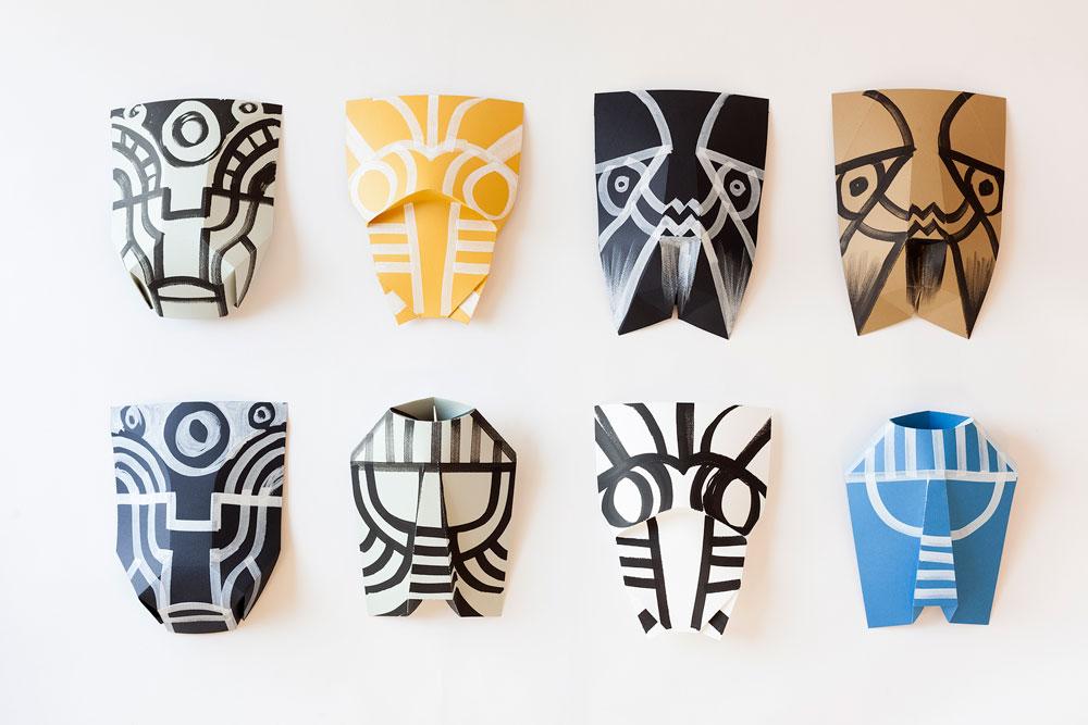 בני-הזוג שירה קרת ואיתי לניאדו והמאייר דקל חברוני יצרו חמישה דגמים של מסכות נייר שנעשו כולן בפורמט זהה – מלבן נייר בסיסי, שקופל לצורה מופשטת של פנים. על המסכה שנוצרה נמשכו שרבוטים ספונטניים בהשפעות אפריקאיות ומרכז־אמריקאיות (צילום: עידו אדן)